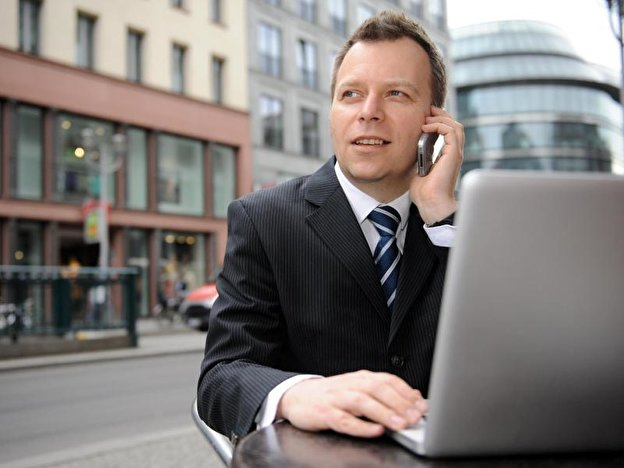 Businessmann mit Laptop und Handy
