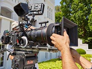 Ein Kameramann greift an eine Filmkamera