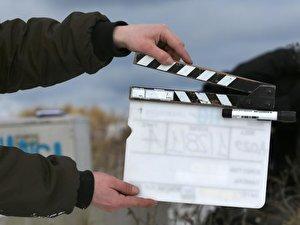 Ein Man hält eine Filmklappe
