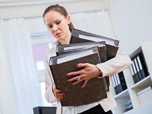 Eine Frau trägt mehrere Aktenordner