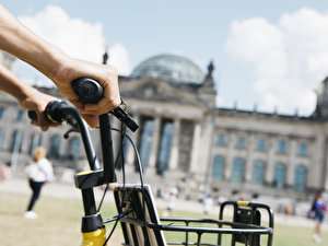 man riding a bike in front of the Reichstag
