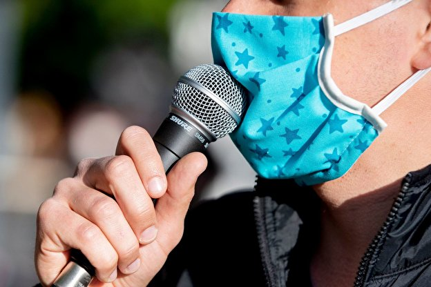 A demonstrator speaks into a microphone wearing a mouth guard.
