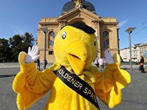 Das Goldene-Spatz-Maskottchen  posiert vor dem Theaterhaus