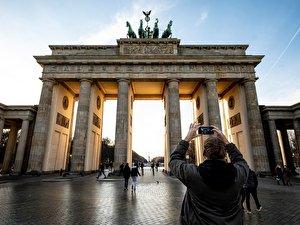 Ein Mann fotografiert bei sonnigen Wetter das Brandenburger Tor