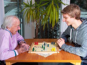 Ein Jugendlicher spielt mit einer Seniorin ein Brettspiel