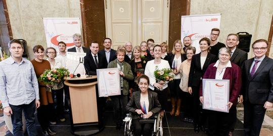 Die Preisträger des Berliner Inklusionspreises stehen gemeinsam auf der Bühne und schauen in die Kamera