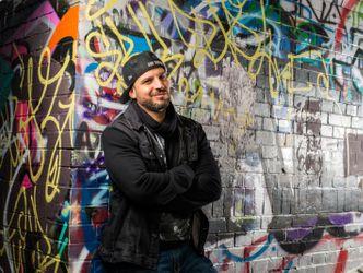 Bildvergrößerung: Ben Salomo vor einer Graffitiwand