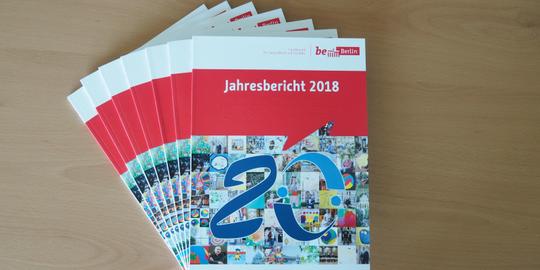Auf einem Tisch liegen aufgefächert ein paar Exemplare vom Jahresbericht 2018