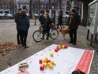"""Zwei Männer und zwei Frauen stehen vor dem Eingang des Rathauses und unterhalten sich. Auf dem Boden liegt eine Plane mit der Aufschrift """"Dragonerareal - was wünscht sich der Kiez?"""" Darauf verteilt liegen bunte Würfel mit Hinweisen von Bürgerinnen."""