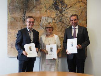 Die drei Behördenchefs stehen mit dem unterzeichneten Kooperationsvertrag vor einem Gemälde.