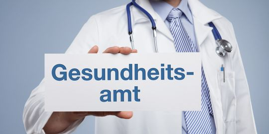"""Arzt hält Schild mit der Aufschrift """"Gesundheitsamt"""""""