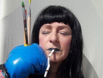 Frau mit schwarzer Perücke hat eine lange Zigarette im Mund und bekommt einen Boxhandschuh mit Pinseln ins Gesicht gehalten