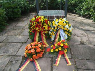 Vier Kränze liegen auf dem Boden vor dem Ehrenmal in der Invalidensiedlung