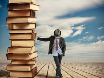 Ein Mann lehnt an einem großen Bücherstapel