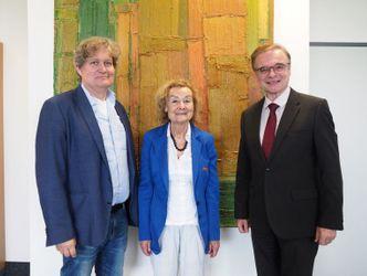 Der Schatzmeister des SoVD Landesverbandes Berlin Brandenburg, Frau Engelen-Kefer und Präsident Allert stehen zusammen vor einem Gemälde.