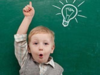 Bildvergrößerung: Kind hebt den Arm vor einer Schultafel auf der eine Glühbirne gezeichnet wurde