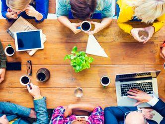 Bildvergrößerung: Acht Menschen sitzen um einen Tisch und unterhalten sich